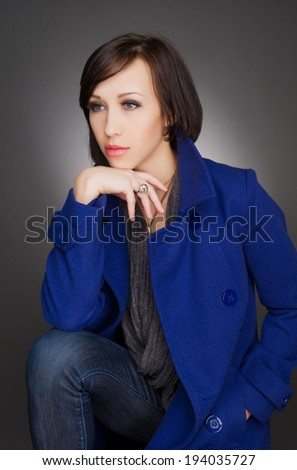 Horizontal color image of a beautiful young woman deep in thoughts. Wearing dark blue winter coat. Studio portrait. - stock photo
