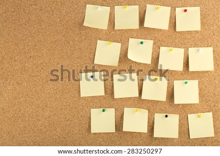 Horizontal cork board with many, yellow sticky notes pinned. - stock photo