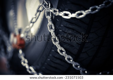 Horizontal detail shot of some new snow chains on a car's tire. - stock photo