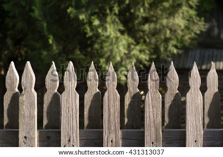 horizontal front view of a wooden fence with a rustic background - stock photo
