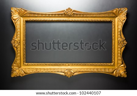 Horizontal golden frame on dark gray, shiny wall. Inner and outer clipping paths included - stock photo