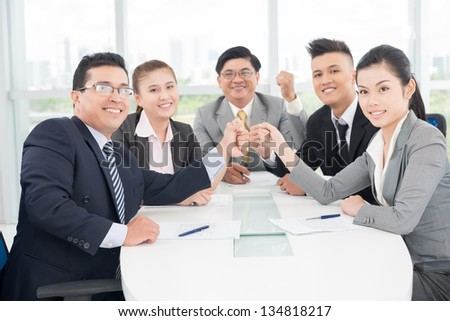 Horizontal image of a business team smiling and looking at camera - stock photo