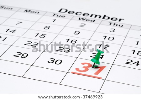 Horizontal image of a calendar with New Year's eve marked with a green tack - stock photo