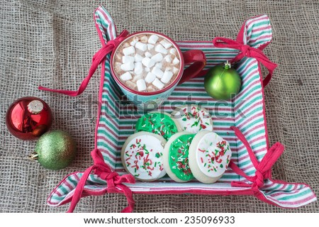 horizontal image of a cloth christmas basket  with a cup of hot chocolate and some short bread cookies covered in white and green icing with sprinkles on a burlap background with two christmas balls. - stock photo