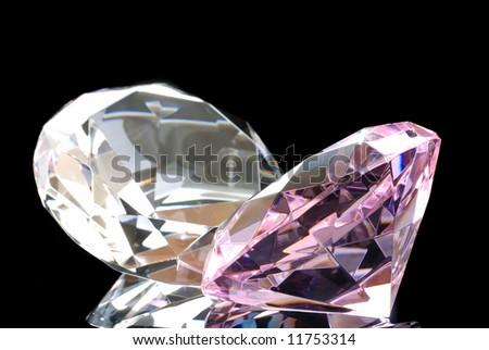 Horizontal Image of a Colored and a Clear Diamond Cut Gems Against a Black Background - stock photo