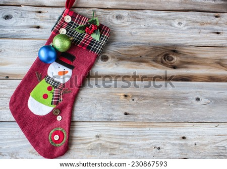 horizontal image of a great idea for christmas card with a red weave stocking with a plaid cuff and a snowman on it adorned with two christmas balls on an old wood knotty background. - stock photo