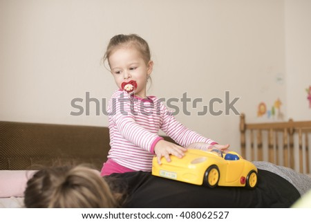 horizontal image of a little girl playing with a yellow toy car on the bedroom bed in her pajamas and pacifier in her mouth while her mother takes a nap - stock photo