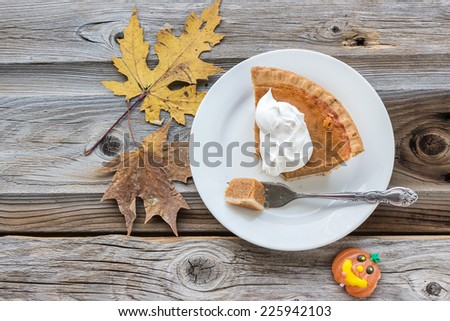horizontal image of a sweet and spicy pumpkin pie topped with whipped cream with a piece cut with fork on a wood surface and background adorned with maple leaves and a pumpkin candy. - stock photo