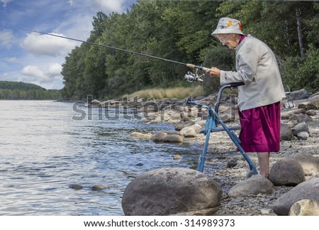 horizontal image of an elderly senior woman with a walker fishing at the edge of the lake with trees and rocks lining the shoreline in the summer time  - stock photo