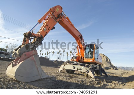 Horizontal image of an excavator (aka rubber duck or digger) in front of a large heap of asphalt. - stock photo