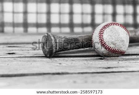 horizontal image of black and white with selective color of a baseball and bat on a wood surface with a checkered background with room for text.  - stock photo