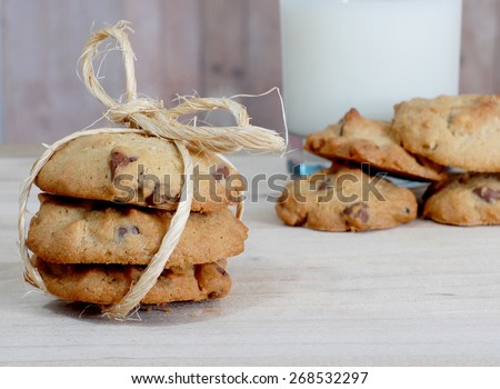Horizontal image of chocolate ship cookies and a glass of milk on a wooden table. Three of the cookies are tied with twine. There are several other cookies next to the milk. Shallow depth of field - stock photo