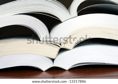Horizontal image of four open books stacked upon each other so their spines more or less nest into the next book. - stock photo