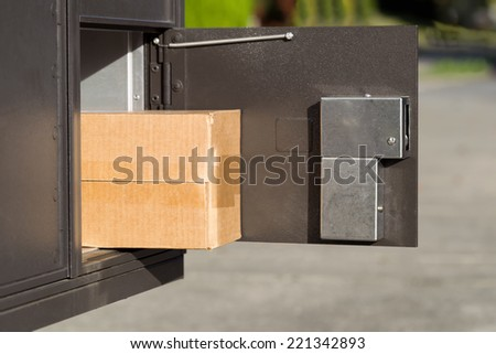 Horizontal image of large package sticking out of postal mailbox with green grass and sidewalk in background  - stock photo
