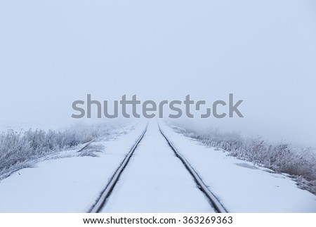 horizontal image of snow covered train tracks leading into a thick fog, with copy space / Train Tracks leading into the Fog - stock photo