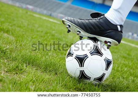 Horizontal image of soccer ball in green grass with foot of player touching it - stock photo