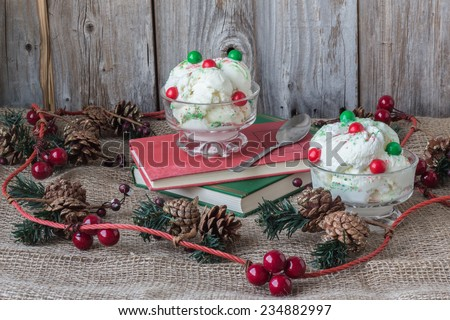 horizontal image of two bowls of ice cream with green and red bubblegum balls on top  sitting on two books with pine cones and decorative cranberries on burlap with an old wood plank background - stock photo