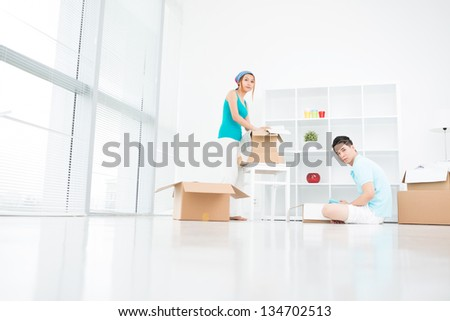Horizontal image of young couple busy with unpacking things - stock photo