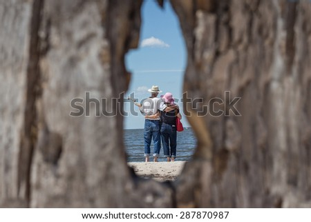 horizontal image taken through a hole in an old oak tree of a man and woman standing in an embrace on the sandy beach looking out across the lake on a warm summer day. - stock photo