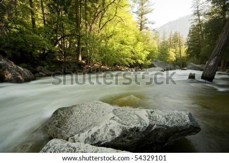 Horizontal landscape image of the Merced river near Mirror Lake in Yosemite taken with a long exposure to get blurry / misty water. - stock photo