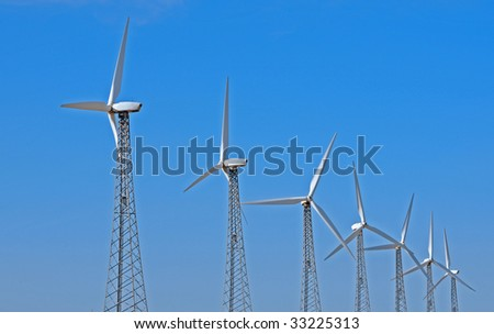 horizontal of a row of wind turbines against a blue sky - stock photo