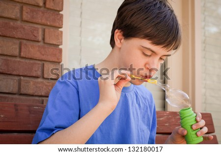horizontal orientation close up of boy with autism and down's syndrome outside playing with bubbles and copy space / Bubbles as Sensory Play - stock photo
