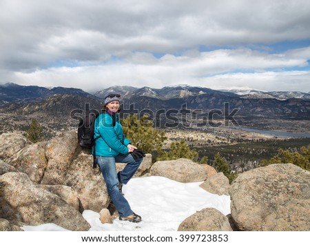 horizontal orientation color image of a happy, smiling, woman hiker with spectacular views of the Rocky Mountains in the background/ Winter Hiker at 9,000 feet - stock photo
