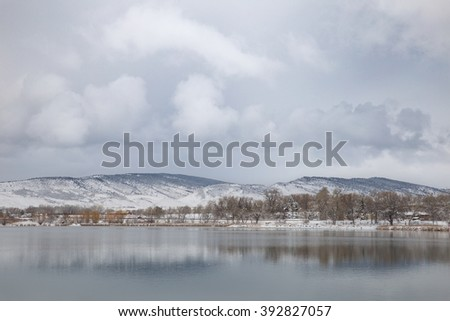 horizontal orientation color image of mountain foothills on a cloudy day with their reflection in a lake in the foreground / Peaceful Reflections on a Cloudy Day - stock photo