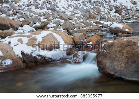 horizontal orientation color image, taken with a very slow shutter speed to show the movement of water in a partly frozen creek in winter / Snow Covered rocks and Waterfall - stock photo
