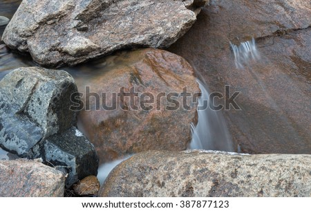 horizontal orientation color image, taken with a very slow shutter speed, to show the movement of water along a rocky creek in Colorado / Winter Waterfall and Boulders - stock photo