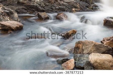 horizontal orientation color image, taken with a very slow shutter speed, to show the movement of water along a rocky creek in Colorado /  Winter Scenery - Creek and boulders - stock photo