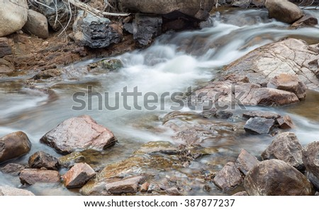 horizontal orientation color image, taken with a very slow shutter speed, to show the movement of water along a rocky creek in Colorado /  Hiking in Winter alongside a Rocky Creek - stock photo
