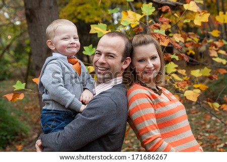 horizontal orientation of a happy, smiling, man, woman and child in the park with brightly colored trees (fall season) in the background / Fall Family Outing - stock photo