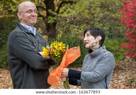 horizontal orientation of a man looking skeptical while a woman offers him flowers / Please Forgive Me! - stock photo