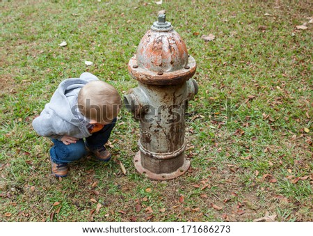 horizontal orientation of a toddler boy stooping to look inside a vintage, rusted fire hydrant in  a field of green grass / What's in there? - stock photo