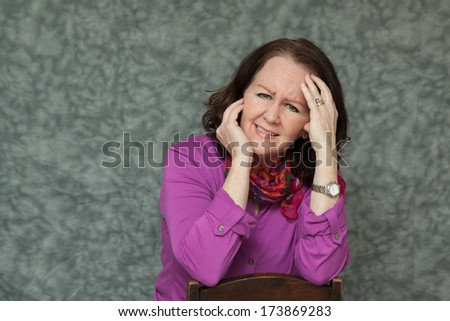 horizontal orientation of a woman in brightly colored business attire grimacing and holding her head with both hands / Migraine Pain - stock photo