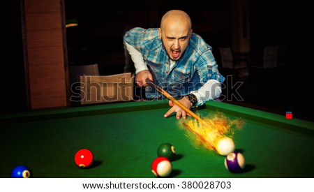 horizontal photo angry man hits fireball at pool billiard. American pool billiard. Pool billiard game. Billiard sport concept. - stock photo