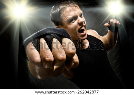 horizontal  photo  muscular young  guy street-fighter, cuff  fist close up on camera and yell , hard light - stock photo