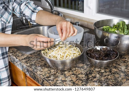 Horizontal photo of female Hands cleaning bean sprouts, with Chinese wood ears, and Choy on top of kitchen counter next to stainless steel sink with plastic strainer - stock photo