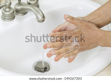 Horizontal photo of female hands rinsing soap off with running water and bathroom sink in background - stock photo