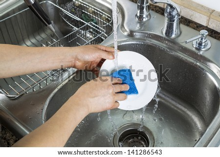 Horizontal photo of female hands washing a small white dinner plate with kitchen sink and running faucet in background - stock photo