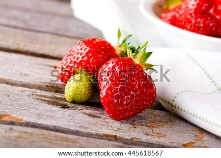 Horizontal photo of few juicy strawberries. Single un-ripe green berry with other with red color. Bowel full of ripe strawberries on towel and wooden board with worn surface. - stock photo