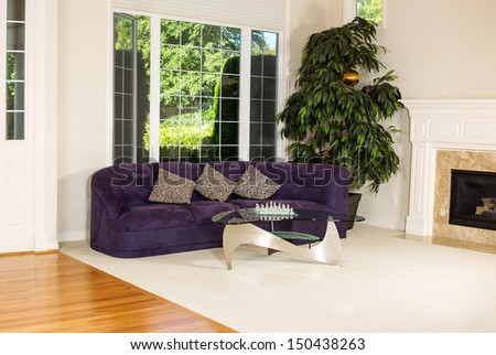 Horizontal photo of formal living room with suede leather couch, glass table, carpet, large windows, plant, fireplace and hard wood floors - stock photo