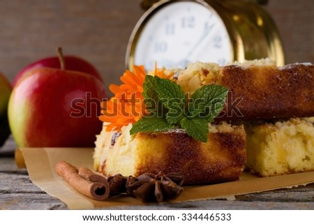 Horizontal photo of fresh baked apple pie on sheet of brown paper with few apples, cinnamon, anise star, marigold, melissa and alarm clock. All is on old grey wooden board.  - stock photo