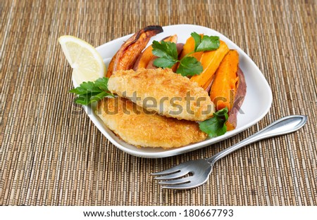 Horizontal photo of fried golden breaded coated fish and yams on white plate - stock photo