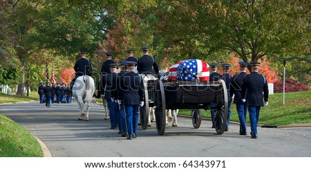 Horizontal photo of Honor Guard at Arlington National Cemetery marching with caisson carrying casket to grave site - stock photo