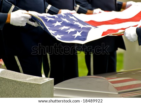 Horizontal photo of honor guard holding flag over casket at Arlington National Cemetery - stock photo
