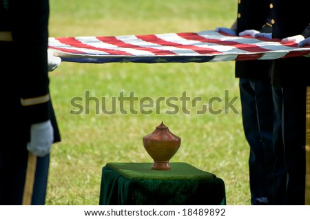 Horizontal photo of honor guard holding US flag over urn at Arlington National Cemetery - stock photo