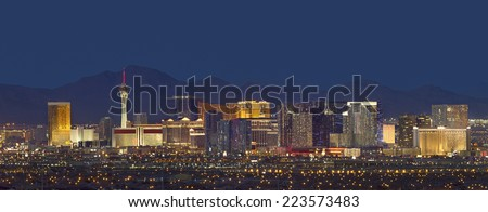 Horizontal photo of Las Vegas with mountain backdrop at night. - stock photo