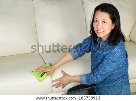 Horizontal photo of mature woman, looking forward, cleaning white leather sofa with microfiber rag in hand  - stock photo